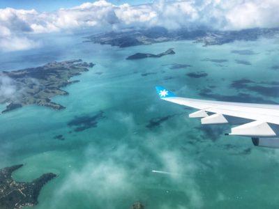 aile d'avion au-dessus d'un océan turquoise et d'îles néo-zélandaises