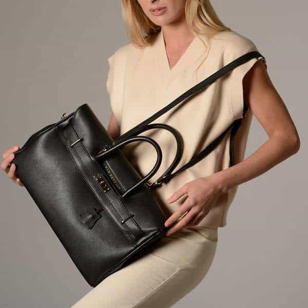 Gros plan d'un sac en cuir noir dans les mains d'une femme