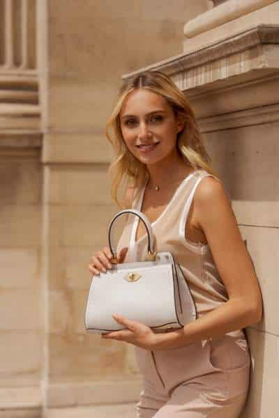 Jeune femme d'affaires portant un sac à main blanc
