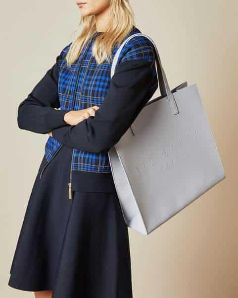 Femme en robe avec un sac à main gris