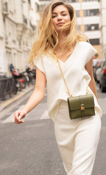 Femme d'affaires avec un sac à main vert dans une ville.