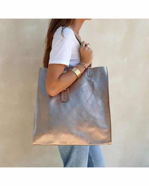 Femme à la mode avec un sac à main métallisé et des chaussures assorties.